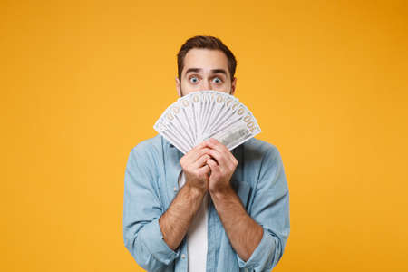Shocked young man in casual blue shirt posing isolated on yellow orange background in studio. People lifestyle concept. Mock up copy space. Covering face with fan of cash money in dollar banknotes.
