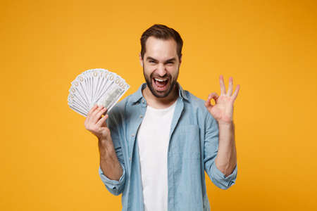 Laughing young man in blue shirt posing isolated on yellow orange background in studio. People lifestyle concept. Mock up copy space. Holding fan of cash money in dollar banknotes, showing OK gesture. Reklamní fotografie