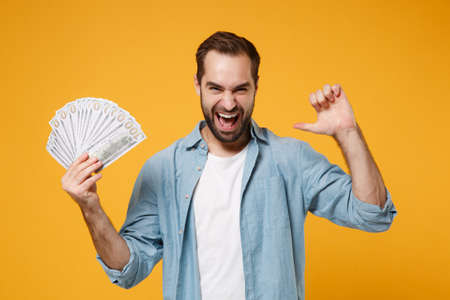 Laughing young man in blue shirt posing isolated on yellow orange wall background. People lifestyle concept. Mock up copy space. Hold fan of cash money in dollar banknotes, pointing thumb on himself.
