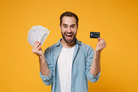 Excited young man in casual blue shirt posing isolated on yellow orange wall background. People lifestyle concept. Mock up copy space. Holding fan of cash money in dollar banknotes, credit bank card. Reklamní fotografie