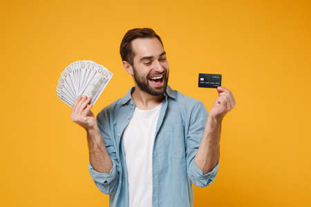 Cheerful young man in casual blue shirt posing isolated on yellow orange wall background. People lifestyle concept. Mock up copy space. Holding fan of cash money in dollar banknotes, credit bank card.
