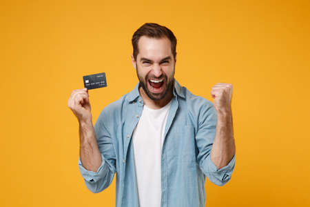 Joyful young man in casual blue shirt posing isolated on yellow orange wall background in studio. People lifestyle concept. Mock up copy space. Hold credit bank card, doing winner gesture, screaming. Reklamní fotografie