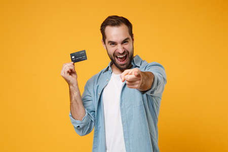Laughing young man in casual blue shirt posing isolated on yellow orange wall background in studio. People lifestyle concept. Mock up copy space. Hold credit bank card pointing index finger on camera.