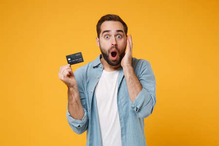 Shocked young man in casual blue shirt posing isolated on yellow orange background, studio portrait. People emotions lifestyle concept. Mock up copy space. Hold credit bank card, keeping mouth open.
