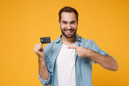 Smiling young man in casual blue shirt posing isolated on yellow orange background, studio portrait. People emotions lifestyle concept. Mock up copy space. Pointing index finger on credit bank card.