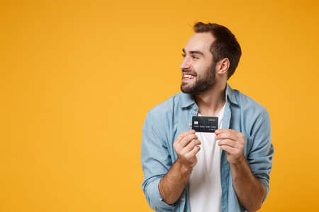 Smiling young man in casual blue shirt posing isolated on yellow orange background, studio portrait. People emotions lifestyle concept. Mock up copy space. Holding credit bank card, looking aside. Reklamní fotografie