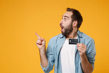 Shocked young man in casual blue shirt posing isolated on yellow orange background in studio. People emotions lifestyle concept. Mock up copy space. Hold credit bank card, pointing index finger aside. Reklamní fotografie