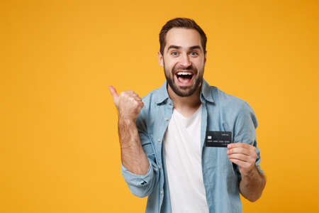 Excited young man in casual blue shirt posing isolated on yellow orange background, studio portrait. People emotions lifestyle concept. Mock up copy space. Hold credit bank card, pointing thumb aside.