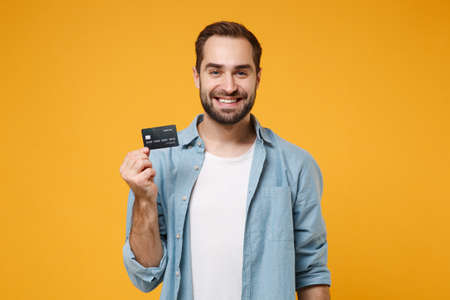 Smiling young man in casual blue shirt posing isolated on yellow orange wall background, studio portrait. People sincere emotions lifestyle concept. Mock up copy space. Hold in hand credit bank card.