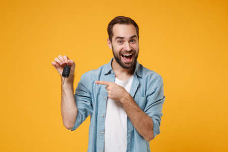 Excited young man in casual blue shirt posing isolated on yellow orange background, studio portrait. People sincere emotions lifestyle concept. Mock up copy space. Pointing index finger on car keys.