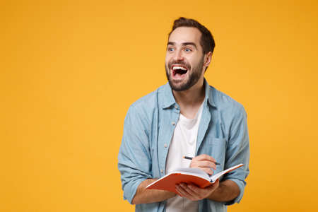 Excited young student man in casual blue shirt posing isolated on yellow orange wall background, studio portrait. People lifestyle concept. Mock up copy space. Writing note in notebook, looking aside.