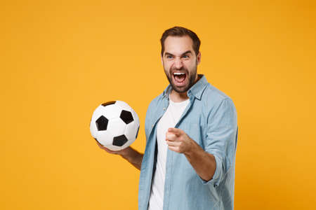 Crazy young man in casual blue shirt posing isolated on yellow orange wall background. People lifestyle concept. Mock up copy space. Hold in hands soccer ball, screaming, pointing index finger aside.