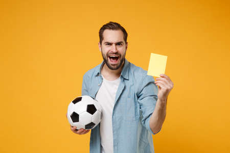 Irritated young man in casual blue shirt posing isolated on yellow orange wall background. People lifestyle concept. Mock up copy space. Hold soccer ball, yellow card propose player retire from field.