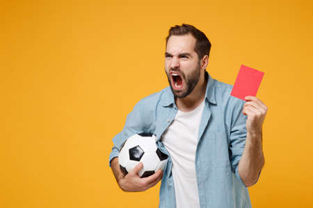 Angry young man in casual blue shirt posing isolated on yellow orange background. People lifestyle concept. Mock up copy space. Hold soccer ball, red card, propose player retire from field, screaming.