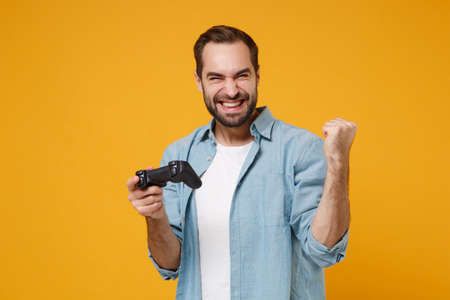 Joyful young man in casual blue shirt posing isolated on yellow orange background, studio portrait. People lifestyle concept. Mock up copy space. Holding joystick playing game doing winner gesture. Banque d'images