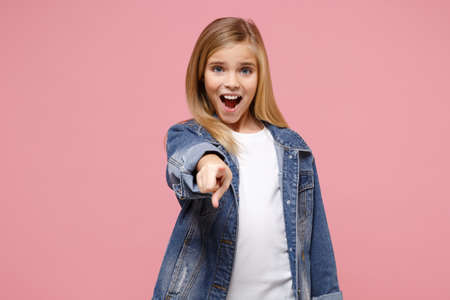 Little blonde kid girl 12-13 years old in denim jacket isolated on pastel pink background children studio portrait. Childhood lifestyle concept. Mock up copy space. Pointing index finger on camera.