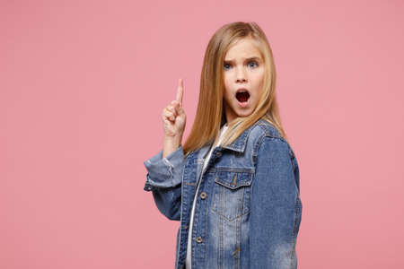 Shocked little kid girl 12-13 years old in denim jacket isolated on pastel pink background in studio. Childhood lifestyle concept. Mock up copy space. Pointing index finger up, keeping mouth open.