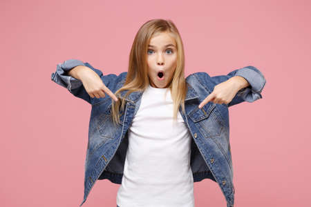 Shocked little blonde kid girl 12-13 years old in denim jacket isolated on pastel pink wall background. Childhood lifestyle concept. Mock up copy space. Pointing index fingers down keeping mouth open.