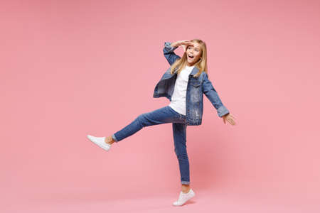 Funny little blonde kid girl 12-13 years old in denim jacket isolated on pastel pink background. Childhood lifestyle concept. Mock up copy space. Holding hand at forehead looking far away distance.