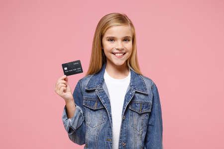 Smiling little blonde kid girl 12-13 years old wearing denim jacket posing isolated on pastel pink background children portrait. Childhood lifestyle concept. Mock up copy space. Hold credit bank card. Reklamní fotografie