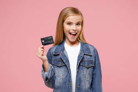 Cheerful little blonde kid girl 12-13 years old in denim jacket posing isolated on pastel pink background children portrait. Childhood lifestyle concept. Mock up copy space. Hold credit bank card.