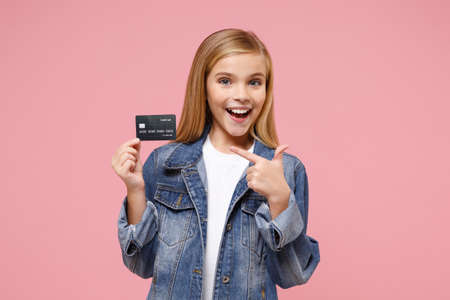 Funny little blonde kid girl 12-13 years old in denim jacket posing isolated on pastel pink wall background. Childhood lifestyle concept. Mock up copy space. Pointing index finger on credit bank card.