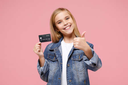 Smiling little blonde kid girl 12-13 years old in denim jacket posing isolated on pastel pink wall background. Childhood lifestyle concept. Mock up copy space. Showing thumb up, hold credit bank card. Reklamní fotografie