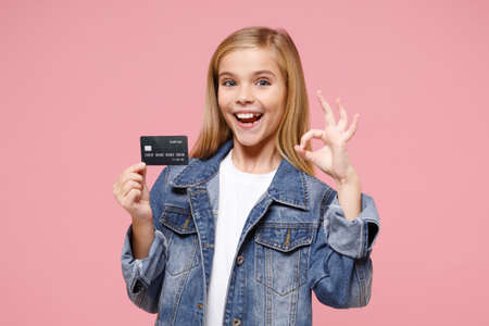 Funny little blonde kid girl 12-13 years old in denim jacket posing isolated on pastel pink wall background. Childhood lifestyle concept. Mock up copy space. Showing OK gesture, hold credit bank card. Reklamní fotografie