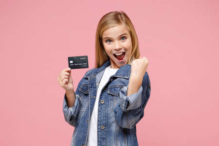 Joyful little blonde kid girl 12-13 years old in denim jacket posing isolated on pastel pink background. Childhood lifestyle concept. Mock up copy space. Doing winner gesture, hold credit bank card.