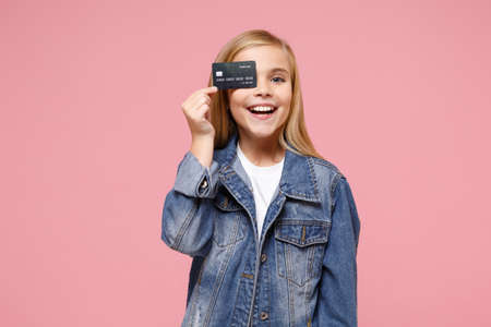 Smiling little blonde kid girl 12-13 years old in denim jacket posing isolated on pastel pink background in studio. Childhood lifestyle concept. Mock up copy space. Covering eye with credit bank card.