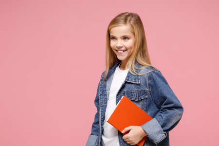 Smiling little kid girl 12-13 years old in denim jacket isolated on pastel pink background children studio portrait. Childhood lifestyle concept. Mock up copy space. Hold book notebook, looking aside.