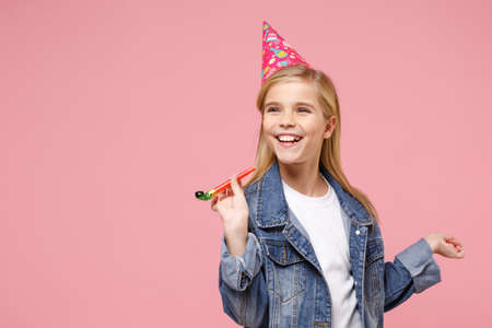 Smiling little blonde kid girl 12-13 years old in denim jacket, birthday hat isolated on pastel pink background. Childhood lifestyle concept. Mock up copy space. Holding party pipe, looking aside.