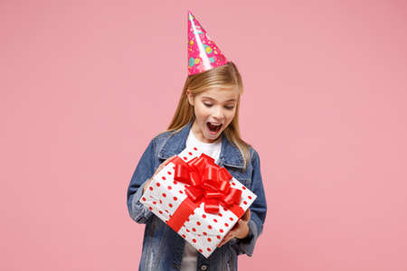 Excited little blonde kid girl 12-13 years old in denim jacket, birthday hat isolated on pastel pink background. Childhood lifestyle concept. Mock up copy space. Hold present box with gift ribbon bow.
