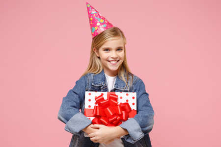 Cheerful little blonde kid girl 12-13 years old in denim jacket birthday hat isolated on pastel pink background. Childhood lifestyle concept. Mock up copy space. Hold present box with gift ribbon bow. Imagens