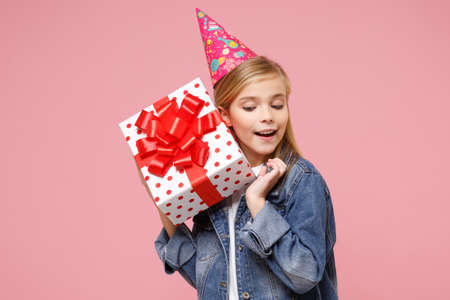 Curious little blonde kid girl 12-13 years old in denim jacket birthday hat isolated on pastel pink background. Childhood lifestyle concept. Mock up copy space. Hold present box with gift ribbon bow. Imagens