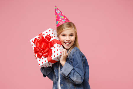 Smiling little blonde kid girl 12-13 years old in denim jacket birthday hat isolated on pastel pink background. Childhood lifestyle concept. Mock up copy space. Hold present box with gift ribbon bow.