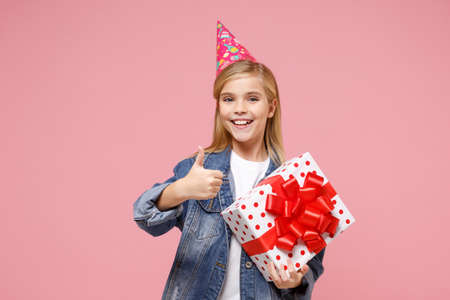 Pretty little kid girl 12-13 years old in birthday hat isolated on pastel pink background. Childhood lifestyle concept. Mock up copy space. Holding present box with gift ribbon bow, showing thumb up. Imagens