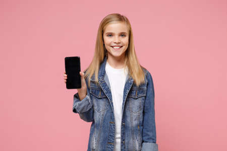 Smiling little blonde kid girl 12-13 years old in denim jacket posing isolated on pastel pink background. Childhood lifestyle concept. Mock up copy space. Hold mobile phone with blank empty screen.