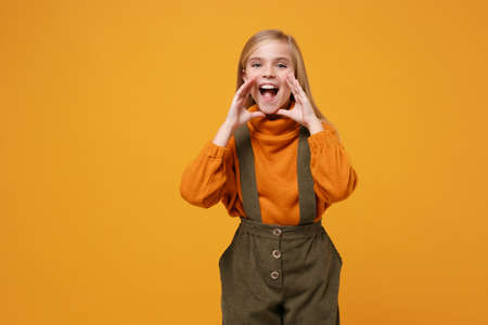Cheerful little blonde kid girl 12-13 years old in turtleneck, jumpsuit isolated on orange yellow background. Childhood lifestyle concept. Mock up copy space. Screaming with hands gesture near mouth. Stock Photo