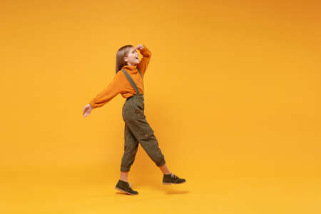 Side view of little kid girl 12-13 years old in turtleneck, jumpsuit isolated on yellow background. Childhood lifestyle concept. Mock up copy space. Holding hand at forehead looking far away distance.