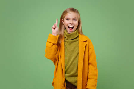 Excited Little blonde kid girl 12-13 years old in yellow coat posing isolated on pastel green background. Childhood lifestyle concept. Mock up copy space. Holding index finger up with great new idea.