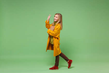 Side view of little girl 12-13 years old in yellow coat posing isolated on green background. Childhood lifestyle concept. Mock up copy space. Hold books, waving greeting with hand as notices someone.