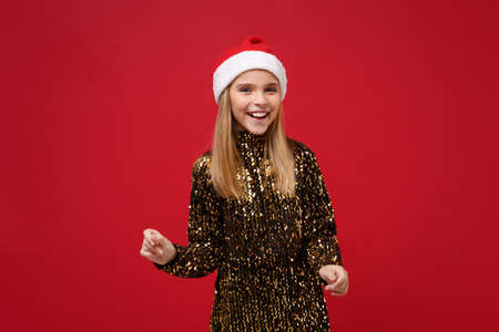 Laughing little blonde kid girl 12-13 years old in glitter party outfit, Santa hat isolated on red wall background. Happy New Year 2020 celebration holiday concept. Mock up copy space. Looking camera.