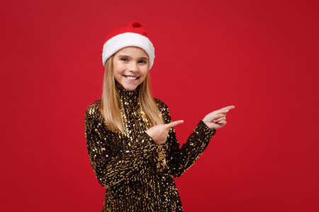 Funny little kid girl 12-13 years old in glitter party outfit, Santa hat isolated on red background. Happy New Year 2020 celebration holiday concept. Mock up copy space. Pointing index fingers aside.