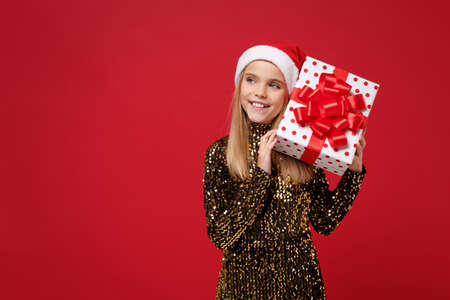 Smiling girl 12-13 years old in glitter party outfit Santa hat isolated on red background. Happy New Year 2020 celebration holiday concept. Mock up copy space. Hold present box with gift ribbon bow.