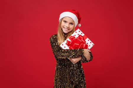 Pretty kid girl 12-13 years old in glitter party outfit Santa hat isolated on red background. New Year 2020 celebration holiday concept. Mock up copy space. Holding present box with gift ribbon bow.