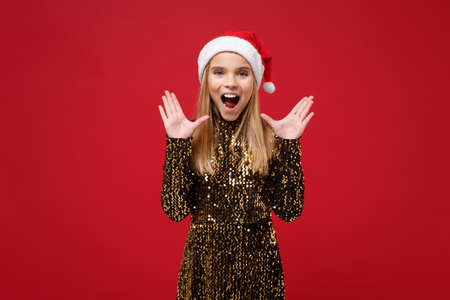Surprised little kid girl 12-13 years old in glitter outfit, Santa hat isolated on red background. New Year 2020 celebration holiday concept. Mock up copy space. Keeping mouth open, spreading hands.
