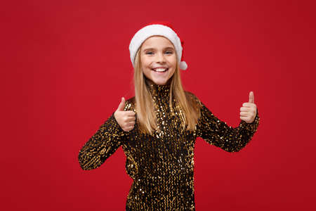 Smiling little blonde kid girl 12-13 years old in glitter party outfit, Santa hat isolated on red background. Happy New Year 2020 celebration holiday concept. Mock up copy space. Showing thumbs up. Stock Photo