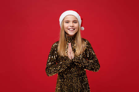 Smiling little kid girl 12-13 years old in glitter party outfit, Santa hat isolated on red background. Happy New Year 2020 celebration holiday concept. Mock up copy space. Hold hands folded in prayer. Stock Photo