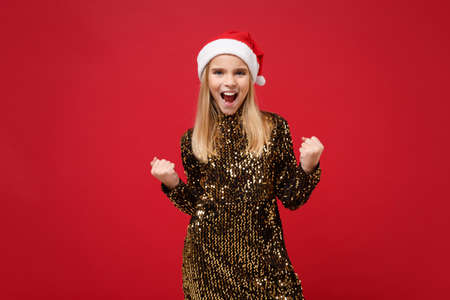 Joyful little kid girl 12-13 years old in glitter party outfit Santa hat isolated on red wall background. New Year 2020 celebration holiday concept. Mock up copy space. Clenching fists like winner.